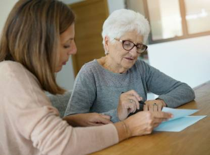 personne-agee-lit-document-avec-aide-PV